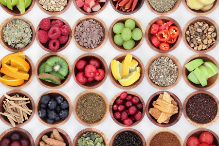 cold cure: Food selection for cold and flu remedy to boost immune system, high in vitamins, anthocyanins, antioxidants and minerals in wooden bowls over white background. Stock Photo
