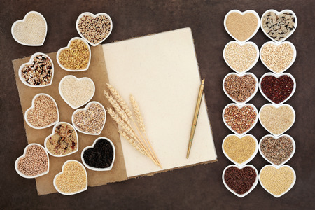 amaranthus: Natural grain health food selection in heart shaped bowls with a hemp paper notebook, wheat sheaths and old pen over lokta paper background.