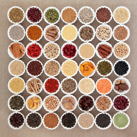 Large dried superfood selection in porcelain china bowls forming an abstract background  over hessian. High in antioxidants, vitamin, minerals and dietary fiber. Stock Photo