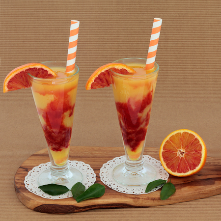 ridged: Blood orange fruit juice drink in glasses on doilies with striped straws on an olive wood board over ridged brown paper background. High in vitamins, anthocyanins and antioxidants.