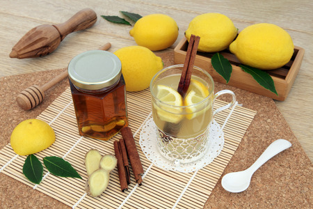 cold remedy: Hot lemon, honey and ginger drink for cold remedy in a glass tea cup with cinnamon stick spice and fresh fruit   on bamboo over cork and oak background.