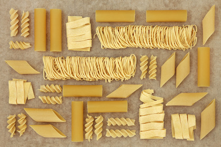 natural selection: Pasta selection forming an abstract background over natural hemp paper background.