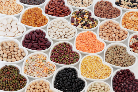 pulses: Dried vegetable pulses health food selection in heart shaped porcelain china dishes over white background.