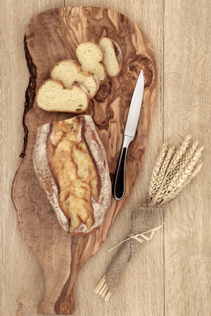 life loaf: Rustic homemade bread loaf with slices on an olive wood board with knife and wheat sheaths in hessian  over oak wood background.