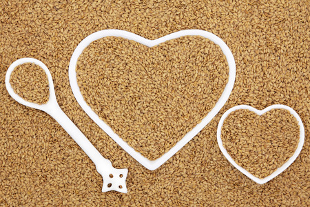 abstract seed: Golden flax seed health food in heart shaped porcelain bowls and spoon forming an abstract background.