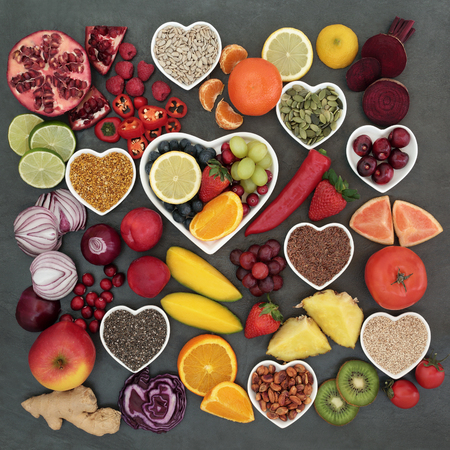 paleolithic: Paleolithic diet health and superfood of fruit, vegetables, nuts and seeds in heart shaped bowls on slate background, high in vitamins, antioxidants, anthocyanins, dietary fiber and minerals.