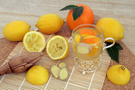 cold remedy: Alternative cold remedy with orange, lemon, ginger spice and honey drink with freshly squeezed fruit on bamboo and cork background.
