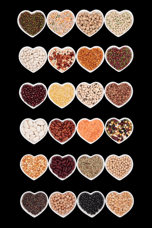 pulses: Dried vegetable pulses health food selection in heart shaped porcelain china dishes over black background.