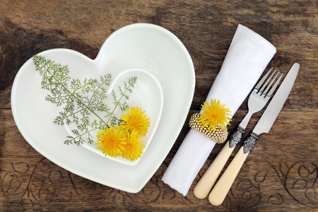 napkin ring: Floral table place setting with white heart shaped porcelain bowls, antique cutlery, dandelion flowers and bronze fennel herb with napkin and ring over old oak background.