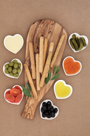 crudite: Crudites selection with bread sticks, mayo and chili dips, olives, oil, gherkins and tomatoes on an olive wood   board.