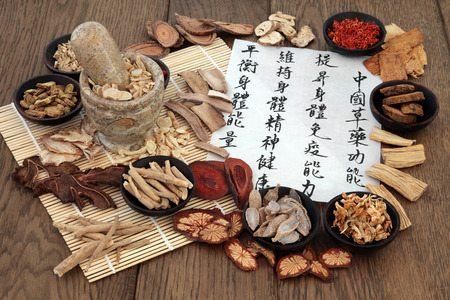Chinese herbal medicine with herb ingredients and calligraphy on rice paper. Translation reads as chinese herbal medicine as increasing the bodys ability to maintain body and spirit health and balance energy.