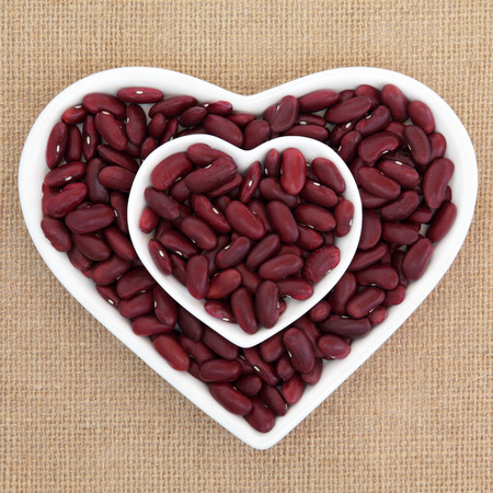 kidney beans: Red kidney beans in heart shaped dishes over hessian background. Stock Photo