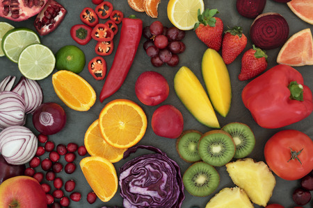 Healthy fresh fruit and vegetable superfood background on slate, high in antioxidants, anthocyanins, vitamins, dietary fiber and minerals.