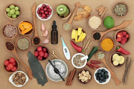 ridged: Alternative medicine and food selection for cold remedy with acupuncture needles, moxa sticks and thermometer over ridged brown paper background.