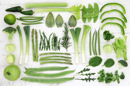 super food: Fresh green super food selection of vegetables and fruits over distressed white wood background, high in antioxidants and vitamins.