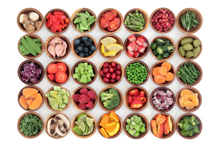 paleolithic: Paleolithic super health food of fruit and vegetables in wooden bowls over white wood background. High in vitamins, antioxidants, minerals and anthocyanins. Stock Photo