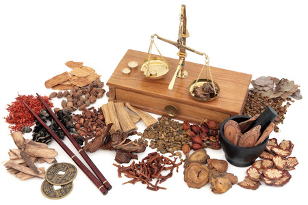Chinese herbal medicine with traditional herb ingredients and old brass scales over white background. Stock Photo