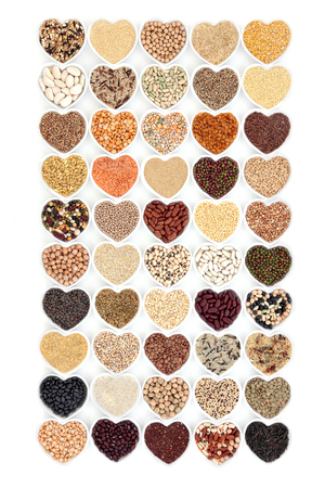 pinto: Grain food and vegetable pulses in heart shaped porcelain bowls over white background.