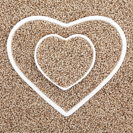 abstract seed: Sesame seed health food in heart shaped porcelain dishes forming an abstract background.