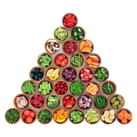 Superfood of fruit and vegetables high in antioxidants, dietary fiber, minerals, anthocyanins and vitamins also used in a paleolithic diet in wooden bowls over white background.