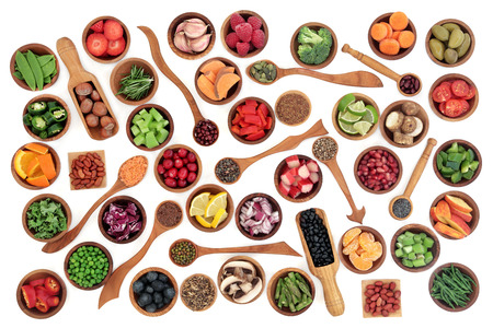 super fruit: Health and super food of fruit, nuts, seeds and vegetables in wooden bowls and spoons over white background, high in vitamins, antioxidants, anthocyanins and minerals.