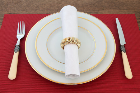napkin ring: Elegant table setting with white gold rimmed porcelain plates, antique cutlery, linen napkin with ring on red placemat on oak table background.