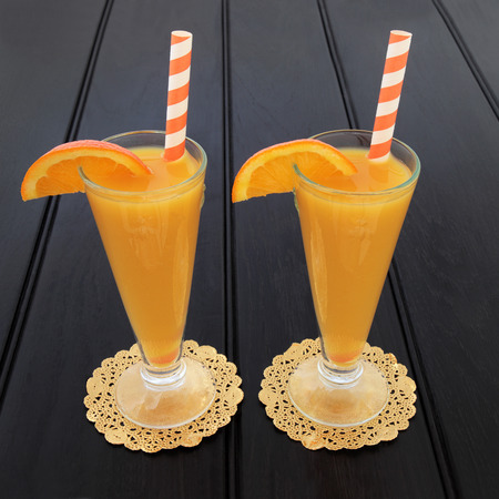 doilies: Orange fruit juice drink in glasses on gold doilies with striped straws over dark wood background. High in vitamins and antioxidants. Stock Photo