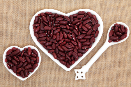 kidney beans: Kidney beans in heart shaped porcelain dishes and spoon forming an abstract background over hessian.