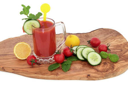 boosting: Tomato juice health drink with lemon, celery, cucumber, basil and mint herb on an olive wood board over white  background. High in vitamins, anthocyanins and antioxidants. Stock Photo