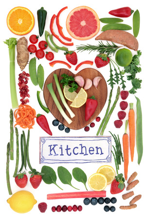 super fruit: Paleolithic super health food of fruit and vegetables on a heart shaped board with old metal kitchen sign over white background. High in vitamins, antioxidants, minerals and anthocyanins.