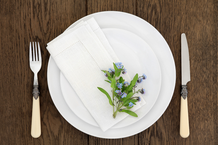 antique dishes: Dinner table place setting with forget me not flowers, white round porcelain dishes and linen napkin with antique cutlery over old oak background.
