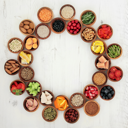 super food: Healthy super food selection in wooden bowls forming a wheel over distressed whte wood background. High in antioxidants, vitamins, minerals and anthocyanins. Stock Photo