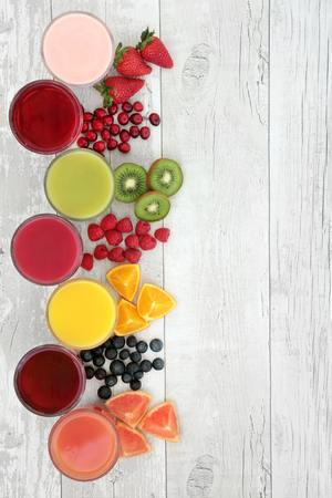 Healthy fresh fruit and juice smoothie drinks over distressed white wood background, high in antioxidants, vitamins, anthocyanins, dietary fiber and minerals. 스톡 콘텐츠