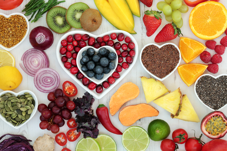 minerals: Paleo diet health and superfood of fruit, vegetables, nuts and seeds in heart shaped bowls on distressed white wood background, high in vitamins, antioxidants, dietary fiber and minerals.