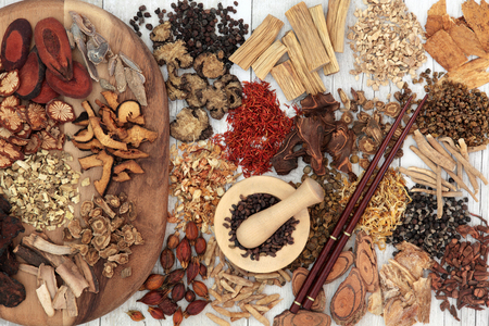 holistic care: Chinese herb selection used in traditional alternative herbal medicine with mortar and pestle and chopsticks over distressed white wood background.