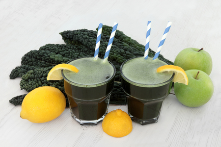 boosting: Kale health drink with fresh vegetable leaves, lemon and apple fruit over distressed white wood background. High in vitamins and antioxidants.