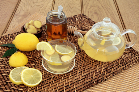 cold remedy: Honey, lemon and ginger drink for cold and flu relief with glass tea cup and pot and fresh fruit on wicker and bamboo mats over oak background.