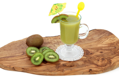 boosting: Kiwi smoothie drink with fresh fruit on an olive wood board over white background. High in vitamins and antioxidants. Stock Photo