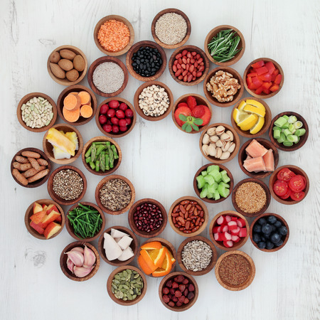 sampler: Healthy super food selection in wooden bowls forming a wheel over distressed white wood background. High in antioxidants, vitamins, minerals and anthocyanins.