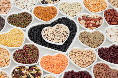 Healthy dried vegetable pulses food selection in heart shaped porcelain china dishes over white background.