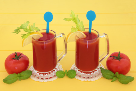 basil herb: Tomato juice health drinks with lemon, celery and basil herb over yellow wood background. High in vitamins, anthocyanins and antioxidants. Stock Photo