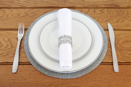napkin ring: Elegant table setting with silver rimmed porcelain plates, stainless steel cutlery, linen napkin with silver ring on   placemat on oak table background. Stock Photo