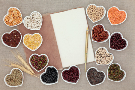 pulses: Dried vegetable pulses health food in heart shaped porcelain dishes on a natural hemp notebook with old pen and wheat sheaths over hessian background. Stock Photo