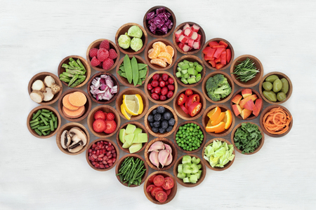 vegan food: Super food for paleolithic diet in wooden bowls over distressed white wood background. High in vitamins, antioxidants, minerals and anthocyanins.