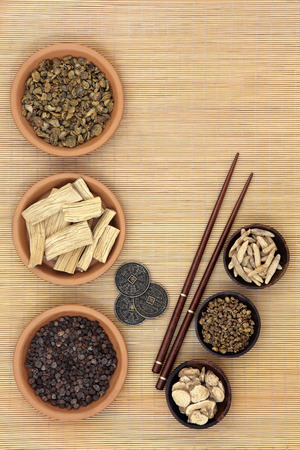 herb medicine: Traditional chinese herb ingredients used in alternative medicine, i ching coins and chopsticks over bamboo background.