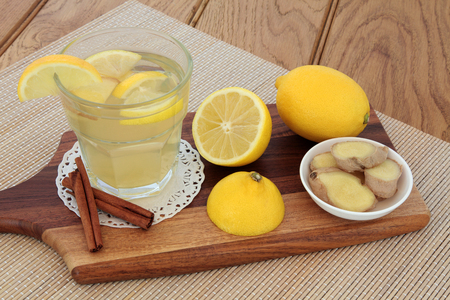soothing: Cold and flu soothing remedy with hot lemon fruit drink, honey, ginger and cinnamon spice on bamboo over oak background.