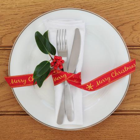 servilleta de papel: ajuste de la tabla con placa de porcelana blanca, cuchillo y tenedor, servilleta de lino, el acebo y la cinta roja Feliz Navidad sobre el fondo de roble.
