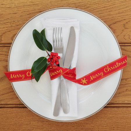 servilleta de papel: Table setting with white porcelain plate, knife and fork, linen serviette, holly and merry christmas red ribbon over oak background.