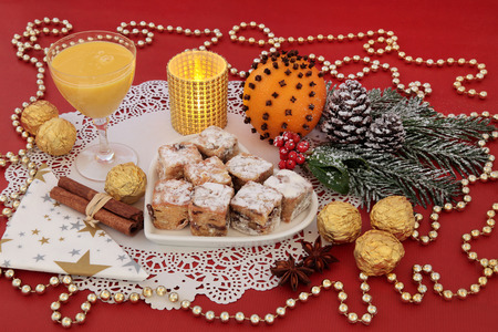 egg nog: Christmas sweet food with stollen cakes, egg nog, foil wrapped chocolates, spices, candle, orange pomander and decorations on a red background. Stock Photo