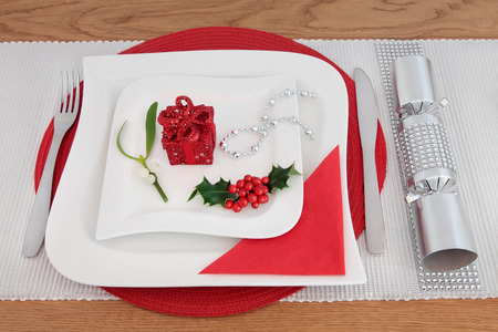 serviette: Christmas dinner decorative table setting with white porcelain plates, cutlery, serviette, holly, mistletoe, gift box decoration, silver cracker with diamond decoration over oak background. Stock Photo